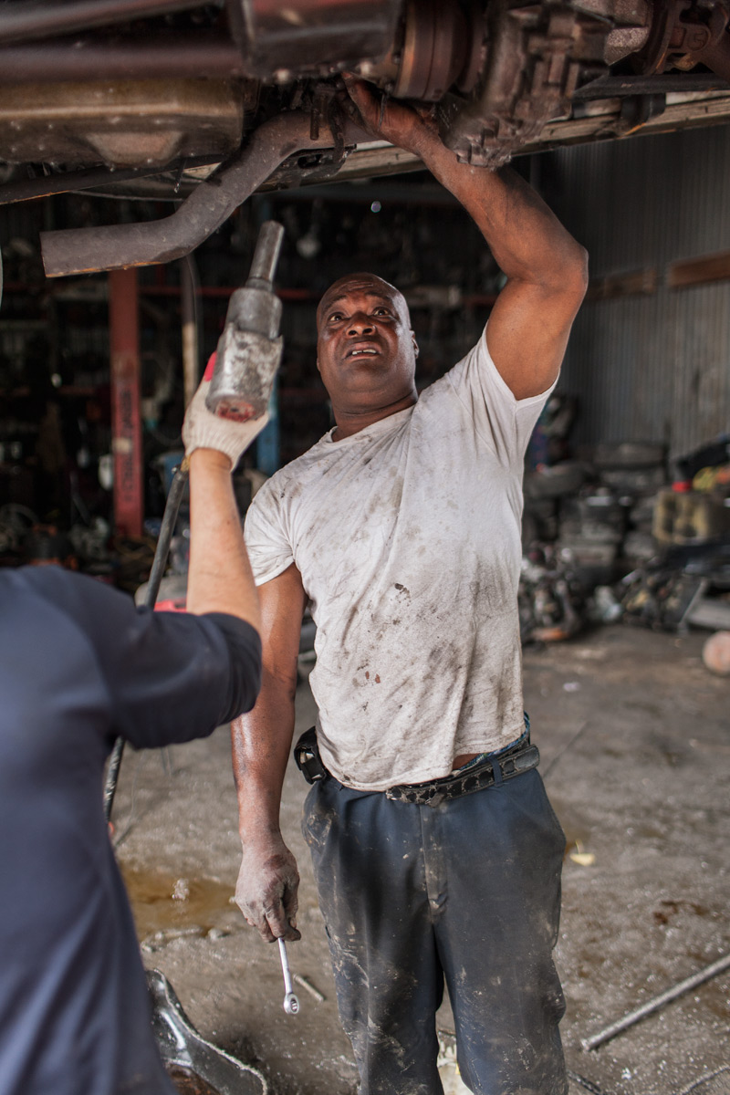 Benny Salvaging a Catalytic Converter, Sunrise Auto Parts. Willets Point, Corona, NY.